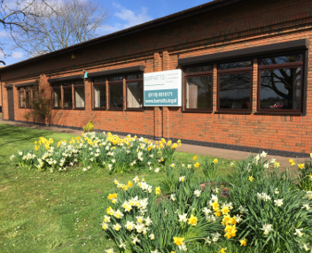 Photo of Barratts office on bright spring day with flowers in the grass