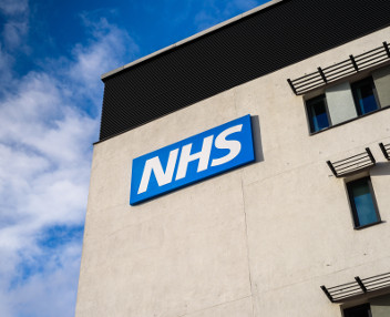 NHS logo as a sign on a building wall