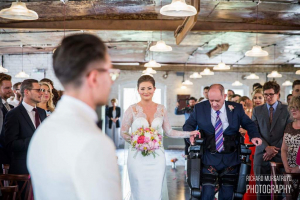 man with spinal injury walking his daughter down the aisle at her wedding